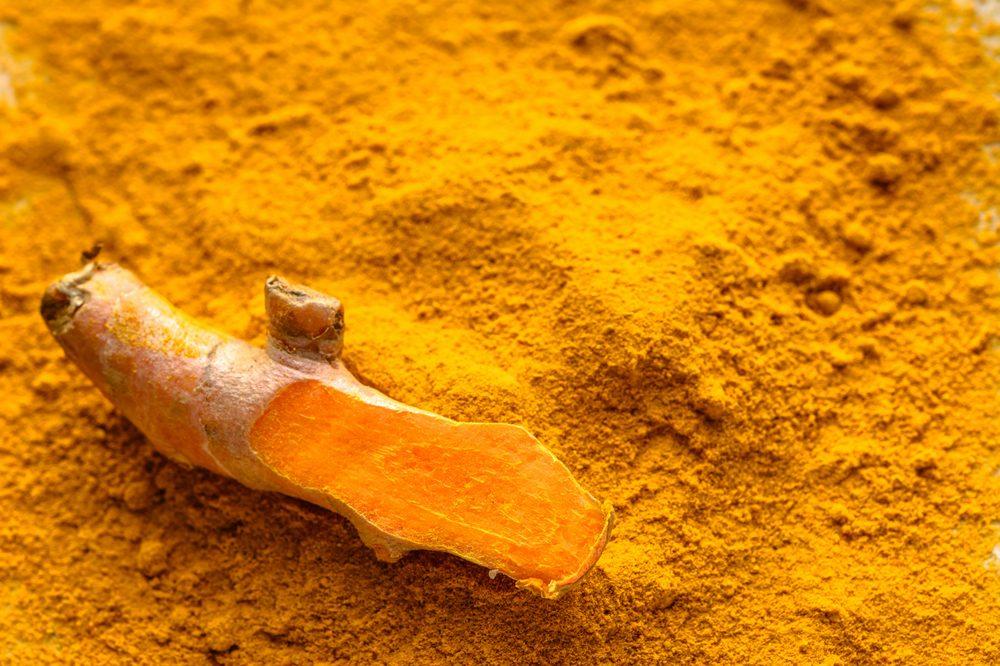 Cut turmeric on a bed of curcumin powder